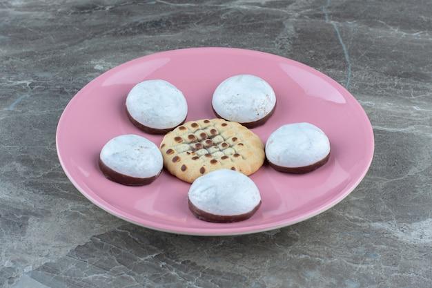 핑크 접시에 신선한 홈메이드 쿠키의 사진을 닫습니다.