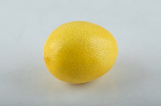 Крупным планом фото свежего лимона на белом фоне.