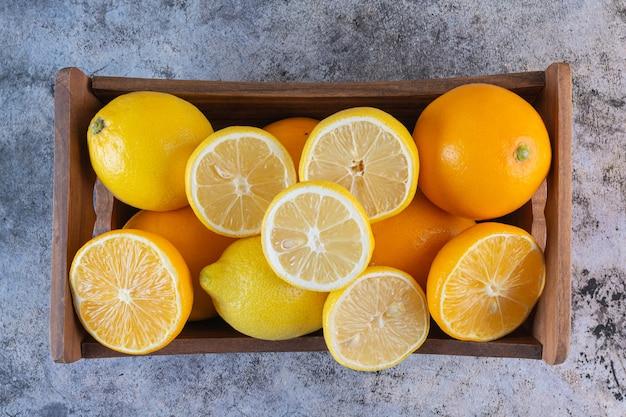Крупным планом фото свежих лимонов в деревянном ящике.