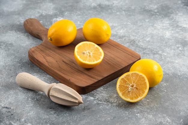 레몬 압착기와 나무 보드에 신선한 레몬의 사진을 닫습니다.