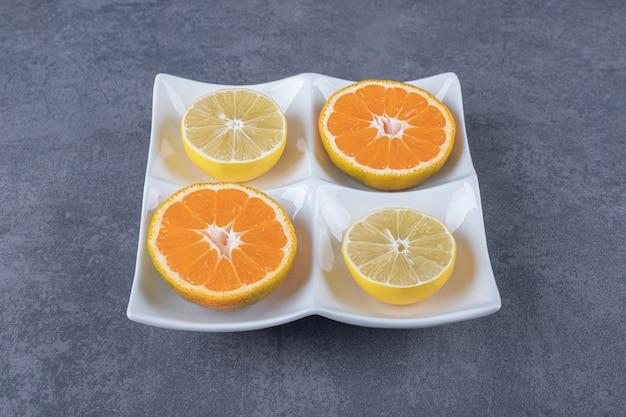白いプレート上の新鮮なオレンジとレモンのスライスの写真を閉じます。