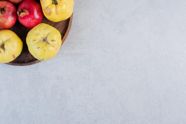 Закройте вверх по фото свежей органической яблочной айвы и граната на деревянной тарелке.
