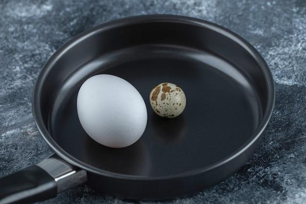 Закройте вверх по фото свежего органического куриного яйца с перепелиными яйцами.