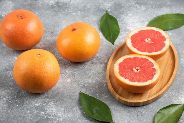 木の板に新鮮な有機グレープフルーツとハーフカットグレープフルーツの写真をクローズアップ。