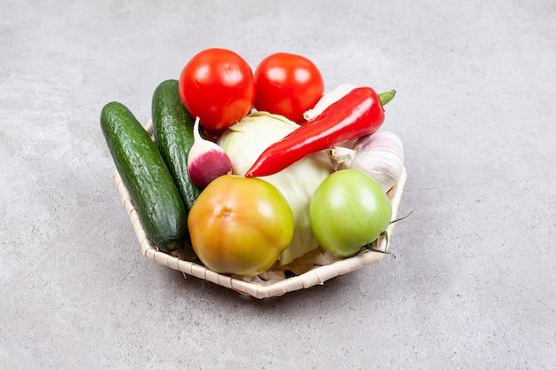 灰色の表面上のバスケットに新鮮な有機野菜の写真を閉じます。