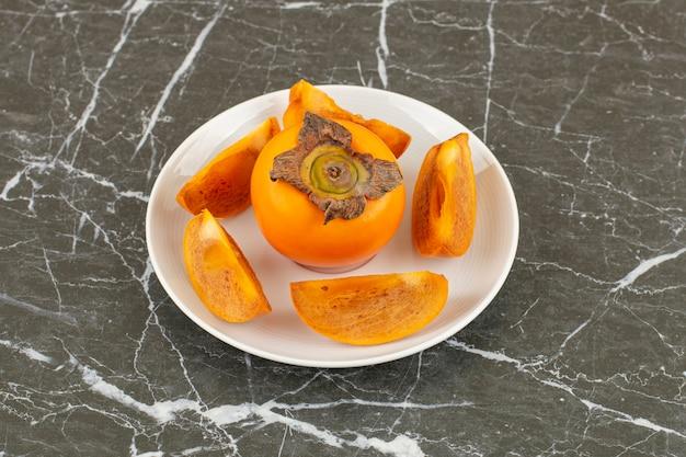 Крупным планом фото свежей хурмы целиком или нарезанной на белой тарелке.