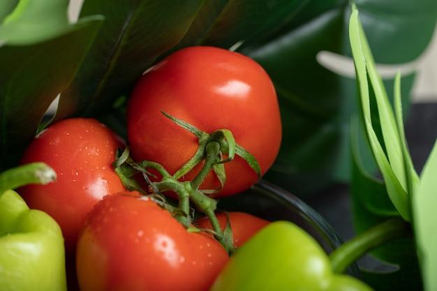 新鮮な完熟トマトとピーマンの写真をクローズアップ。
