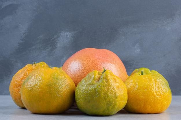 Крупным планом фото свежих мандаринов и грейпфрута.