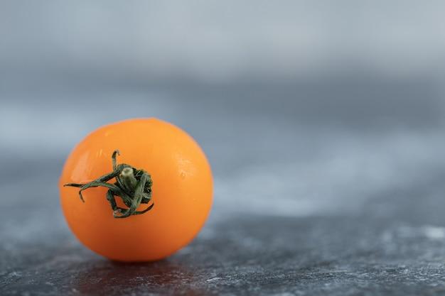 회색 바탕에 신선한 노란색 체리 토마토의 사진을 닫습니다.