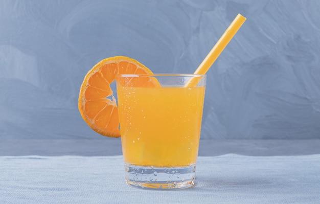 灰色の背景に作りたてのオレンジジュースの写真をクローズアップ。