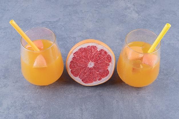 Крупным планом фото свежеприготовленного апельсинового сока со спелым грейпфрутом на сером фоне.