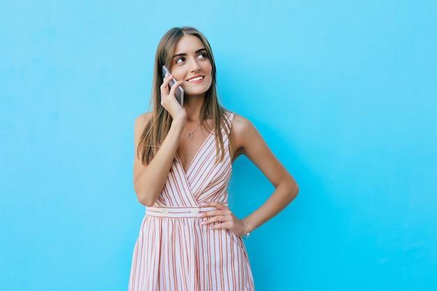 금발 머리를 한 멋진 소녀의 사진을 닫고, 왼쪽을 바라보며 전화 통화를 하면서 기쁨으로 웃고 있습니다.
