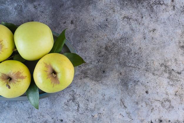 Крупным планом фото зеленых яблок с листьями на сером.