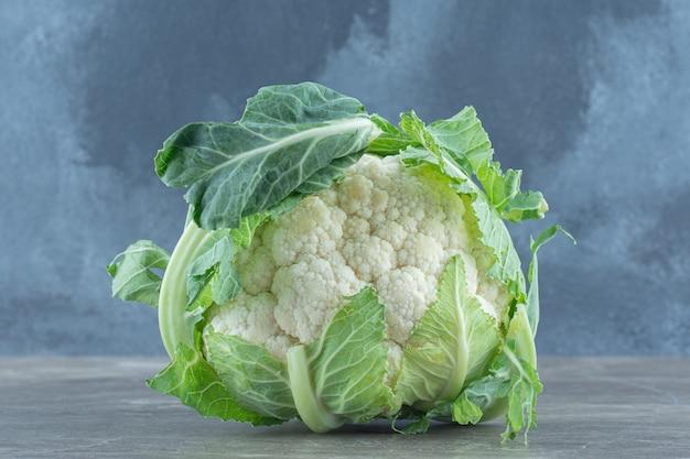 Закройте вверх по фото зеленой свежей цветной капусты на сером столе.