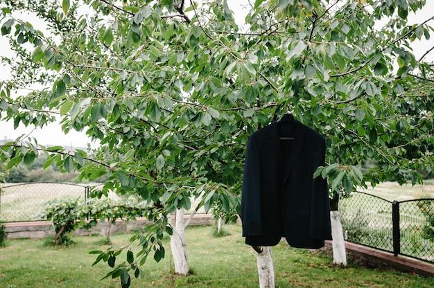 Крупным планом фото пиджак жениха, висящий на ветке дерева на открытом воздухе.