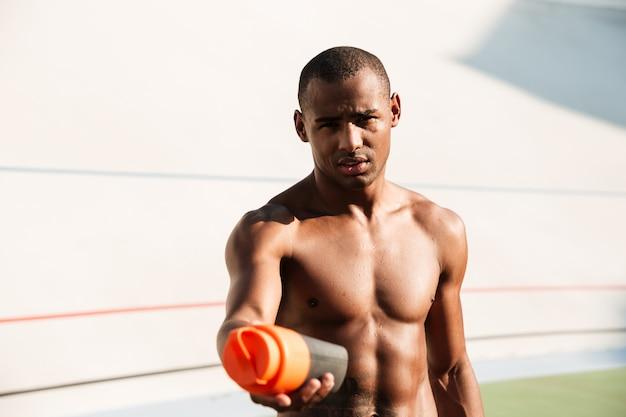 水のボトルを保持している半分裸のアフリカスポーツ男のクローズアップ写真