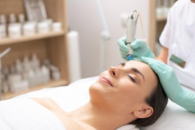 웃는 여자의 얼굴에 특별한 도구로 피부를 청소하는 의료 절차를 수행하는 장갑에 손의 사진을 닫습니다