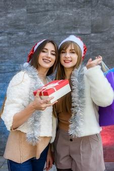 新年のお祝いに彼女の友人にギフトボックスを与える幸せなブルネットの女性のクローズアップ写真