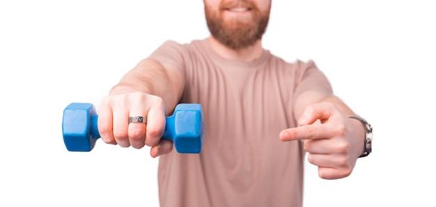白い壁の上の青いダンベルを指している幸せな若い男の写真を閉じる
