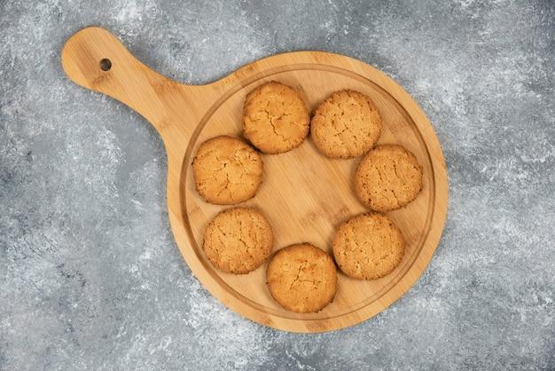 회색 탁자 위의 나무 판자에 있는 집에서 만든 쿠키 사진을 클로즈업하세요.