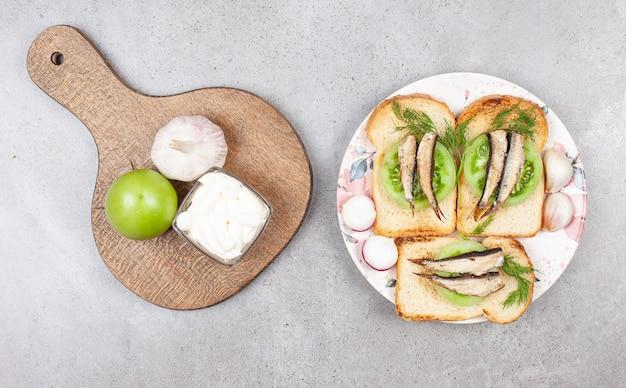 마늘과 설 익은 토마토로 만든 생선 샌드위치의 사진을 닫습니다