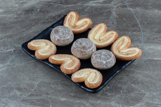 黒いプレートに自家製の新鮮なおいしいクッキーの写真をクローズアップ。