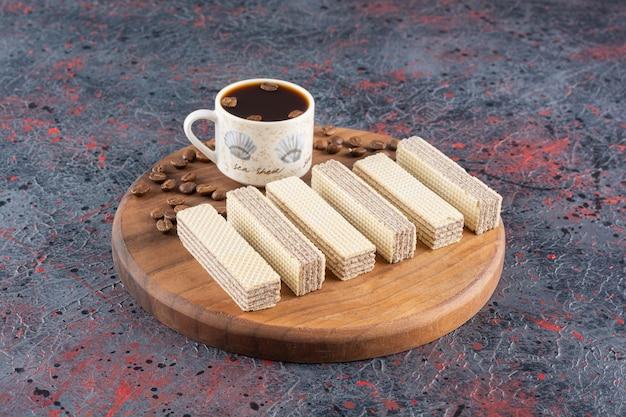 나무 보드에 커피와 원두 커피 한잔과 함께 만든 신선한 웨이퍼의 사진을 닫습니다.