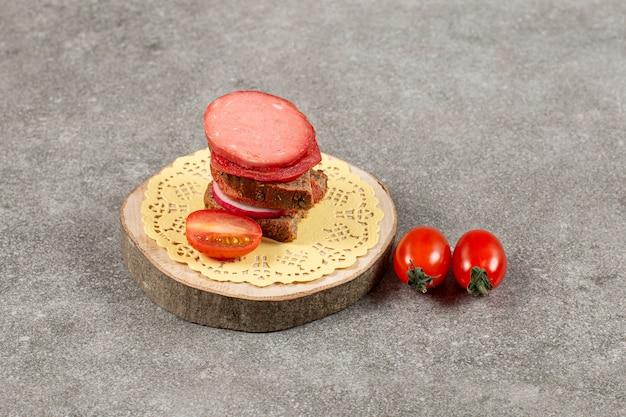 木の板にトマトと自家製サンドイッチの写真をクローズアップ。