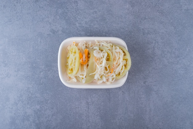 회색 위에 흰색 그릇에 집에서 만든 소금에 절인 양배추의 사진을 닫습니다.