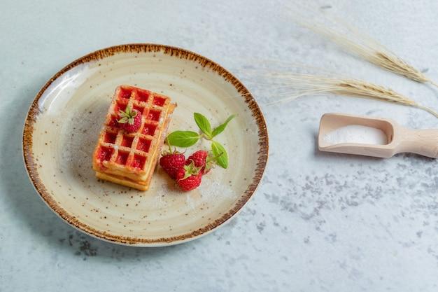 Крупным планом фото домашних вафель со свежей малиной.