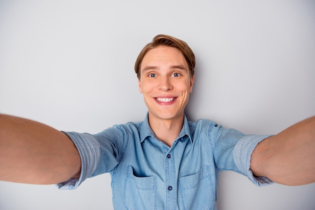 Крупным планом фото импозантного парня, проводящего свободное время в пути, сделайте селфи-видеозвонок в красивом наряде, изолированном на сером фоне