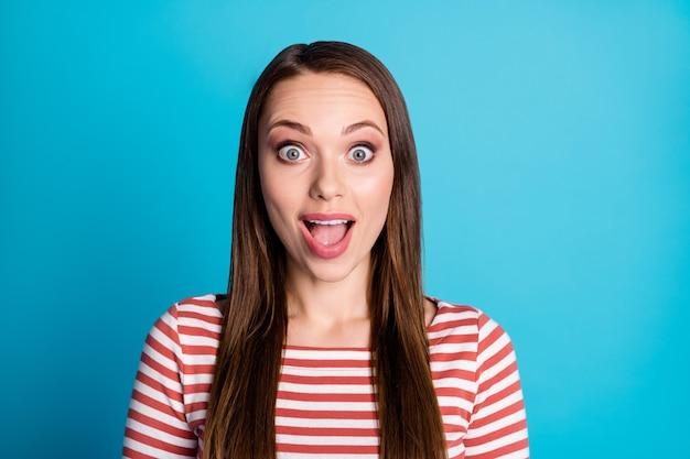 感動した女の子のクローズアップ写真は、青い色の背景の上に分離された素晴らしい販売シーズン割引ノベルティ口を開けて悲鳴を上げるカジュアルなスタイルの服を聞く