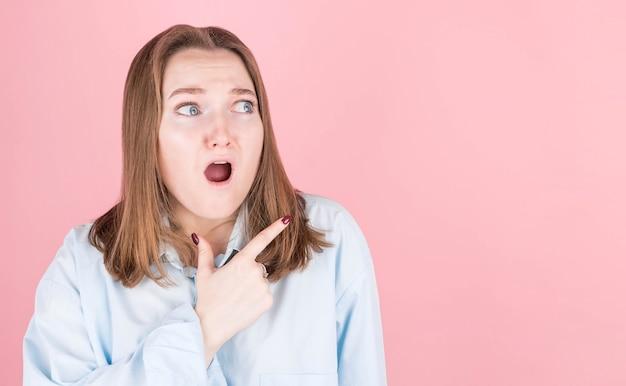 ピンクの青いシャツで推薦の信じられないほどの叫びを示している感銘を受けた女性のクローズアップ写真