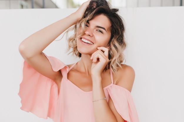 ブロンドのウェーブのかかった髪で遊んでいるインスピレーションを得た日焼けした女の子のクローズアップ写真。夢のような白人女性モデルの肖像画は、流行のピンクの服を着ています。