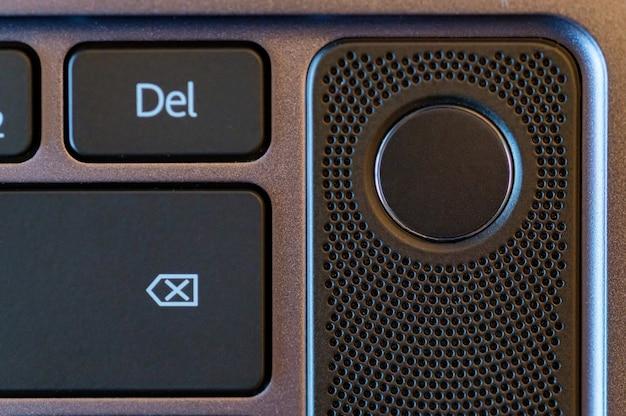 Крупным планом фото кнопки датчика отпечатков пальцев ноутбука