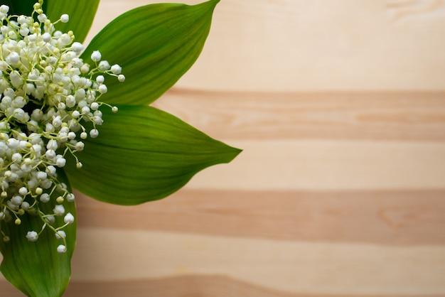 나무 테이블의 은방울꽃 꽃다발의 사진을 닫습니다