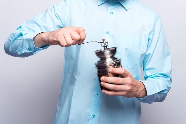 수동 분쇄기로 커피를 분쇄하는 남성 손의 사진을 닫습니다.