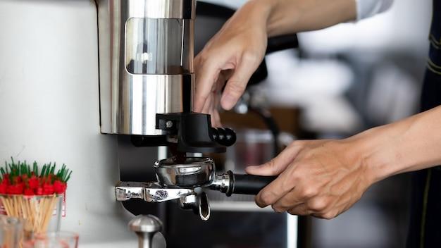 커피숍에서 금속 탬퍼와 포터필터를 들고 있는 남성 손의 사진을 클로즈업하세요. 한 남자 바리스타가 카페에서 에스프레소나 아메리카노를 끓이기 위해 분쇄 커피를 준비하고 있습니다.