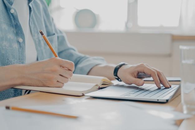コンピューターのキーボードで入力し、議題にメモを書いている男性の手の写真、フリーランスの労働者がメッセージを入力し、台所のテーブルに座って自宅からインターネットでクライアントに連絡している写真を閉じる