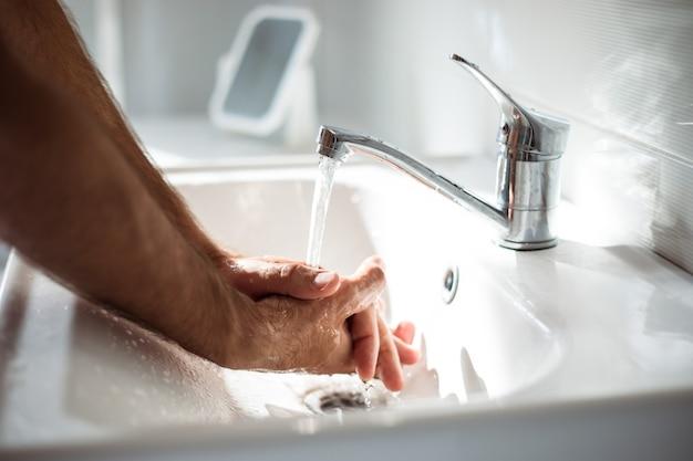 洗面台に石鹸で男性の手の写真をクローズアップ。安全健康処置、パンデミック、抗菌。