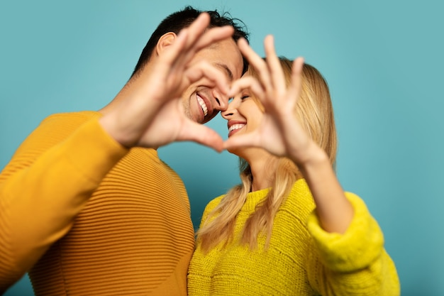 노란 옷을 입은 남녀가 눈을 감고 웃고 있고, 머리를 서로 가까이 두고 손으로 하트를 만들고 있는 클로즈업 사진.