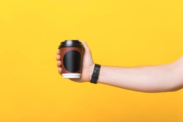 노란색 배경 위에 종이컵의 커피를 들고 있는 남자 손의 사진을 닫습니다