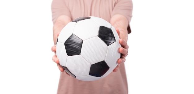 Крупным планом фото человека, держащего футбольный мяч над белой стеной