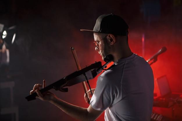 エレクトリック バイオリンのコンセプトを演奏する男のクローズ アップ写真