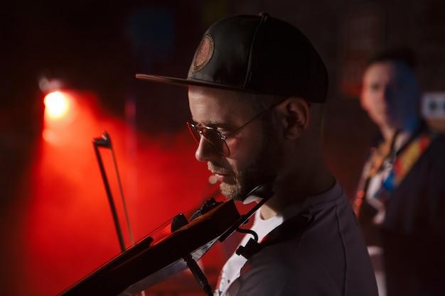 電気バイオリンコンセプトを演奏する男性のクローズアップ写真