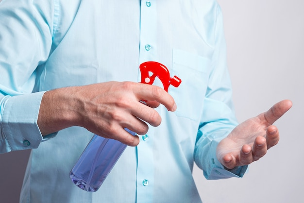 Крупным планом фото человека, распыляющего на руки дезинфицирующее средство для рук во время пандемии.