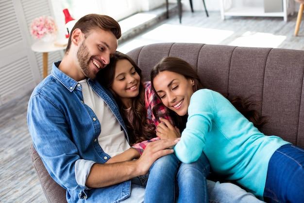 輝く笑顔で抱き締めて、スタイリッシュなリビングルームで共同写真のために一緒にポーズをとっている母、父と娘の写真をクローズアップ