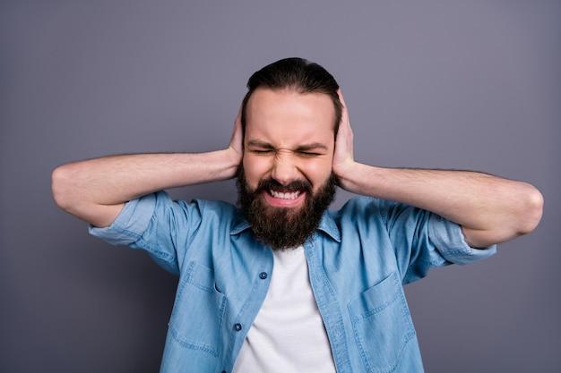 긴장된 불쾌한 화가 분노한 남자의 사진 닫기 커버 귀 닫기 그의 아내 시끄러운 목소리는 회색 벽 위에 고립 된 유행 옷을 입으십시오.