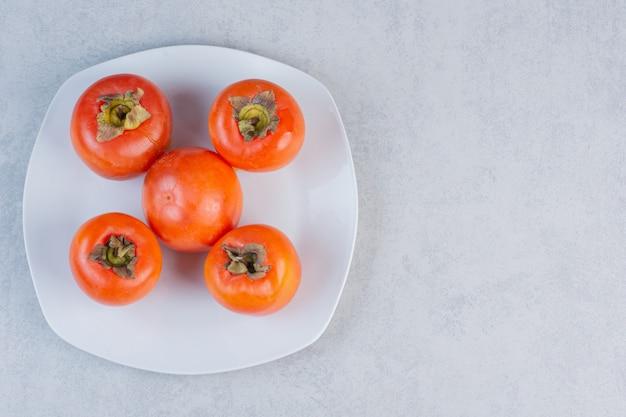 白いプレート上のオレンジ色の柿の写真を閉じます。