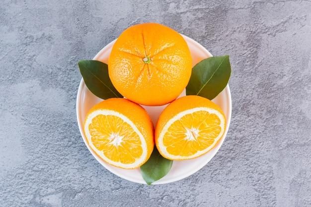 회색 위에 하얀 접시에 유기농 레몬의 사진을 닫습니다.